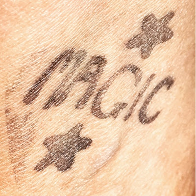 wrist stamp of the word magic and a star above and below