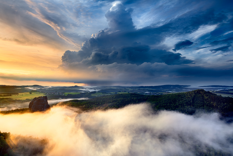 Photo: Elemental Force - A big and dangerous-looking thunderstorm cell is approaching the Saxon Switzerland on a summer day. It has already started to rain at the horizon, while the Falkenstein Mountain in the foreground of the photo still bathes in warm setting sunlight.    For Fine Art Prints and more Work please visit my website: www.richterphotographie.de