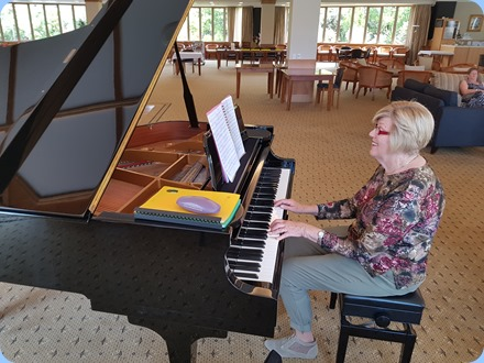 Kay Boyes playing the Kohler and Campbell grand piano.