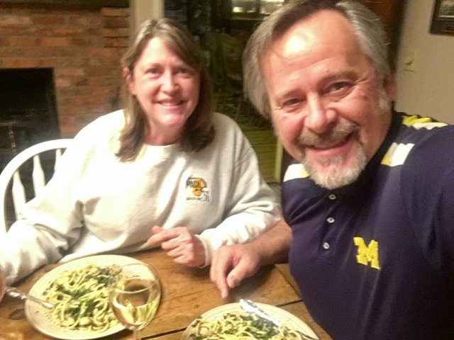 Woman in grey sweatshirt with man in blue polo shirt having dinner of pasta and greens with a glass of white wine