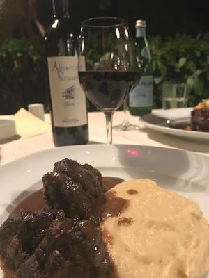 Tallerken med mørkt kjøtt og potetmos. En vinflaske og et glass i bakgrunnen.