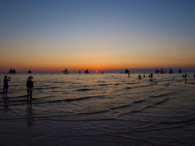 People and sail boat silhouettes at sunset on White Beach, Boracay, Philippines