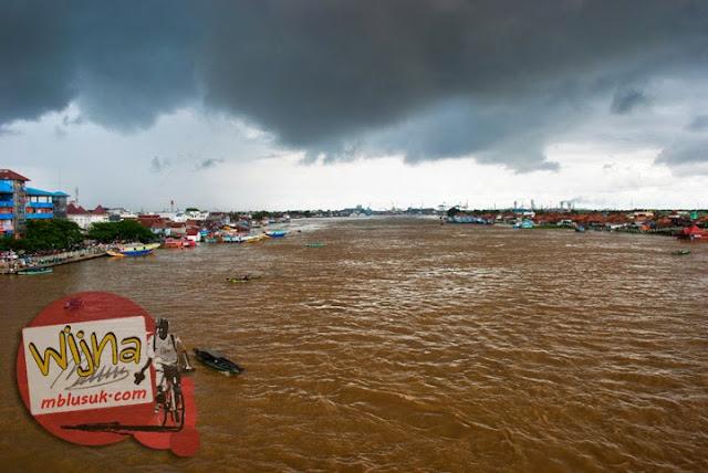 Penampakan Sungai Musi di Kota Palembang Sumatera Selatan yang tercemar dan berwarna coklat keruh dengan latar awan mendung