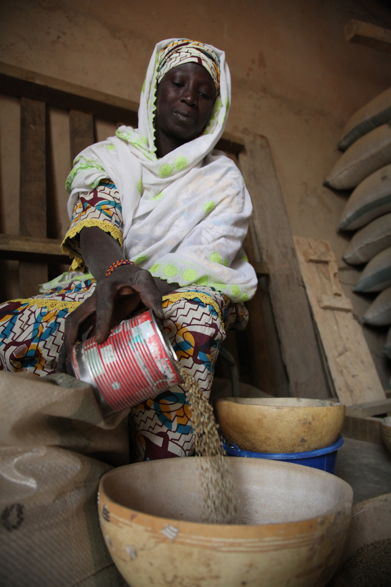 Photo: A woman pours millet into a bowl at a Plan-funded cereal bank in Tillaberi District, Niger.