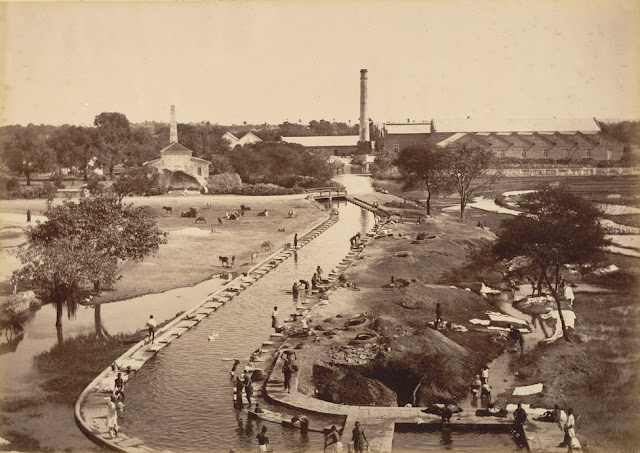 Photograph of mills at Hyderabad, Andhra Pradesh, Curzon Collection: 'Views of HH the Nizam's Dominions, Hyderabad, Deccan, 1892', taken by Deen Dayal in the 1880s. Hyderabad was founded beside the River Musi in 1591 by Muhammad Quli Qutb Shah (r.1580-1612) as an alternative to his capital at Golconda. Later, Hyderabad became the capital of the Nizams of Hyderabad, who ruled over one of the largest states in India. The dynasty was founded by Nizam al-Mulk, entitled Asaf Jah (d. 1748) who arrived in the Deccan as the Mughal governor. In 1724 Asaf Jah declared independence and established the dynasty of Nizams who ruled until 1948. There were no modern industries in Hyderabad before 1874 but a few years later railway workshops were established nearby and four factories sprang up south and east of the Hussain Sagar lake. These industrial units became the centre of new settlements. This is a view of the mills and the nearby canal.