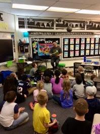 Ian Tadashi Moore reading to a classroom of kids