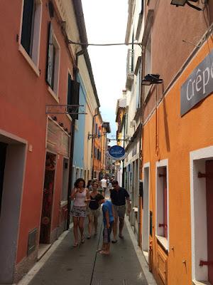 En smal gate med høye, fargerike hus på begge sider.