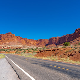 Lonely road in Utah by Bert Templeton - Landscapes Mountains & Hills ( utah, red, moab, blue sky, blue, road, black, lonely, red rock, highway, lonely road,  )