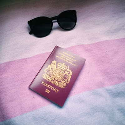 Sunglasses with Birtish passport on bed