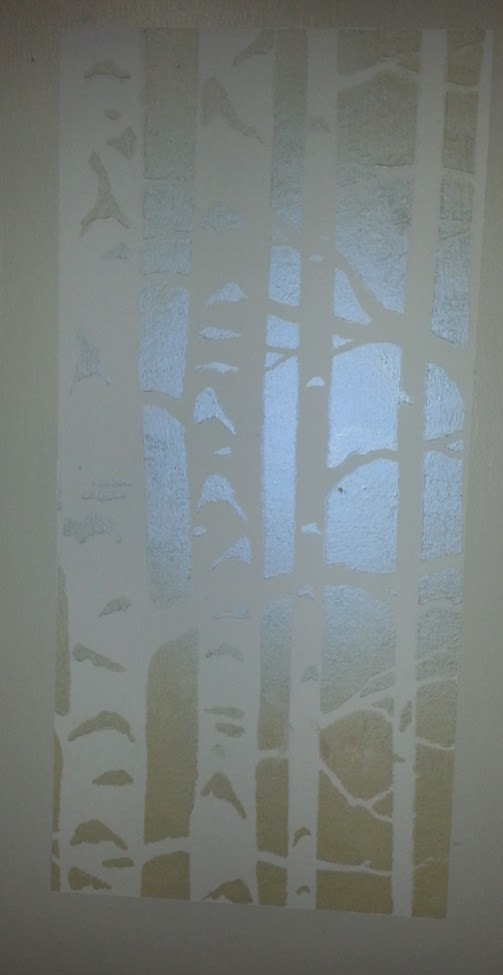A stenciled design on a white wall showing stylized birch tree trunks, with an iridescent blue glow from pearl powder
