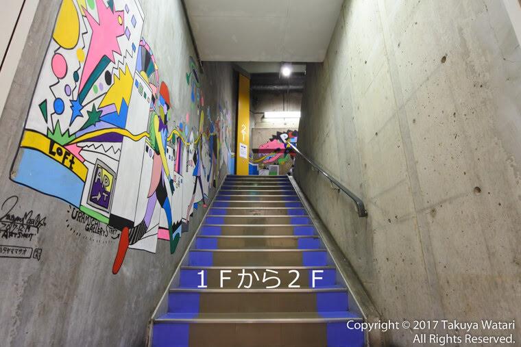 梅田ロフト1階から2階へ続く階段。1Fから2Fと文字を入れてある