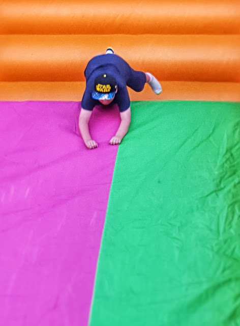 Photo of a boy diving down a multicoloured bouncy slide