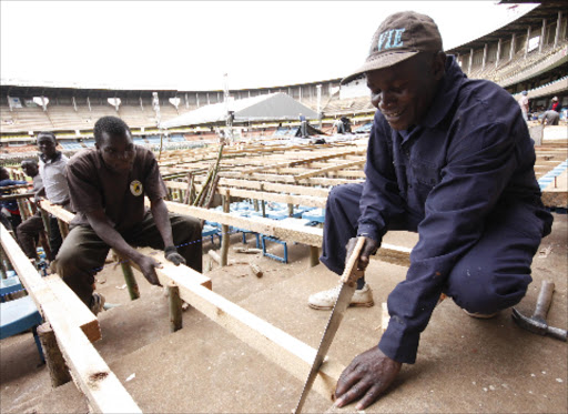 A carpenter cuts a piece of frame during the construction of the dias used during the swearing in ceremony of President elect Uhuru Kenyatta at Kasarani Stadium.