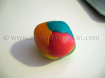 A close up photo of a red, yellow, orange, green and blue cookie dough ball.