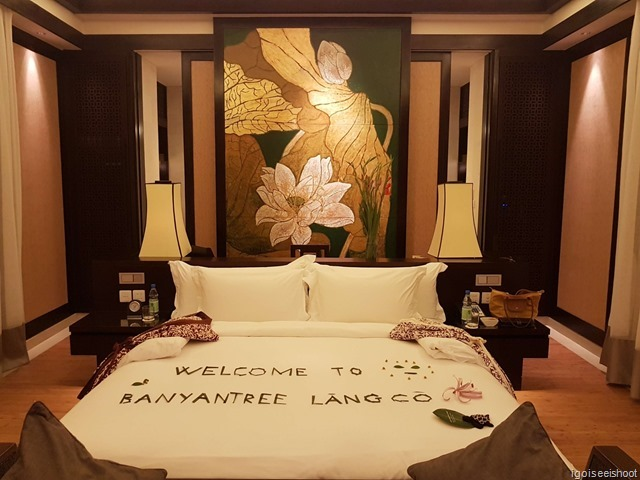 The spacious bedroom of the Beach Villa at Banyan Tree Lang Co with a King size bed. The bath area is behind the large screen with pictures of the lotus flowers, a study area with long writing desk, welcome fruit basket.