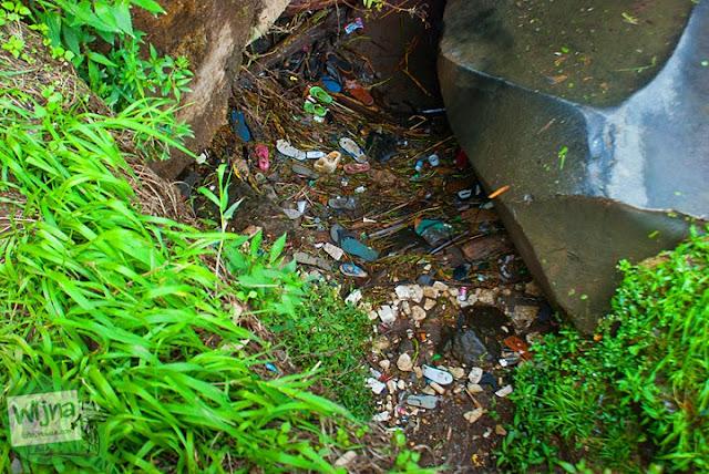 Sampah-sampah berserakan di dasar air Terjun Coban Talun di Kota Batu