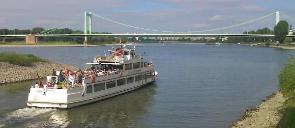 Das Motorschiff »Willi Ostermann« verlässt den Mülheimer Hafen, im Hintergrund die Mülheimer Brücke.