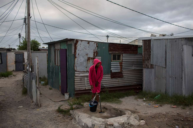 In this 2 February 2018 photo, a woman collects water in a settlement near South Africa's drought-hit city of Cape Town. About a quarter of Cape Town's population lives in the informal settlements, where they get water from communal taps instead of individual taps at home like in the richer suburbs. And they use 4.5 percent of the total water consumption. Photo: Bram Janssen / AP Photo