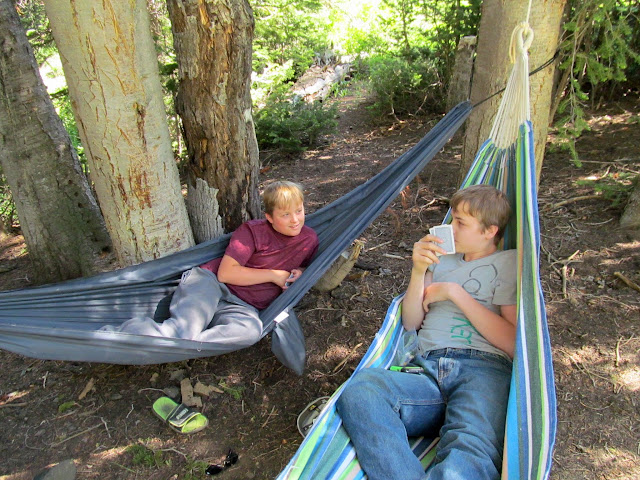 Bradley and Michael lying in hammocks and playing cards