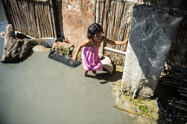 A girl walks through floodwater outside her home in the El Indio settlement on the outskirts of Piura, in northern Peru, in March 2017. Photo: Ernesto Benavides / AFP
