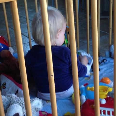 Kind spielt im Laufgitter