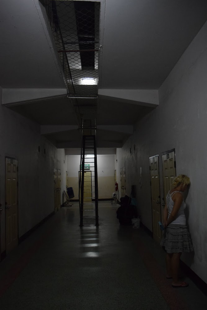 The gloomy halls of our cheap hotel, which Anna remarks look like a prison, complete with chain-link fence covering the space in the ceiling!  Anna takes a prison-yard pose as I snap the photo!