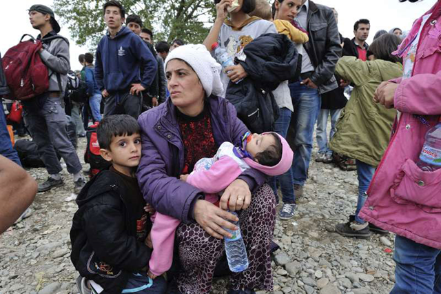 Mother and children waiting with other refugees to enter Vinojug reception centre at Gevgelija, in the former Yugoslav Republic of Macedonia, at the border with Greece. Photo: Mark Henley / UNHCR