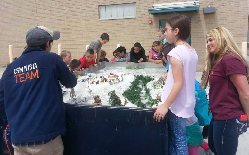 OSMRE/VISTA Conn Fraser instructing Mesa Verde Elementary School students using the San Juan Soil and Water Conservation District's Rolling Rivers trailer, demonstrating hydrological properties such as erosion, river meandering, and watershed science.