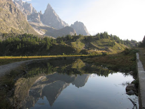 Photo: A lake at the valley floor reflects the great spire of the Aiguille Noir, a side-peak of Mt. Blanc.