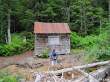B-Spec evaluating the eroded bank beneath the dam cabin.