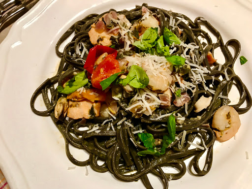 Venetian cuttlefish ink pasta with lightly smoked salmon, prawns, mussels and squid