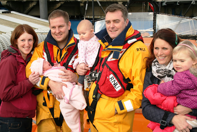 Baby Faye wondering why little Bethan isn't enjoying having her photograph taken as much as her dad likes taking them.  25 January 2014 Photo: RNLI Poole/Rob Inett