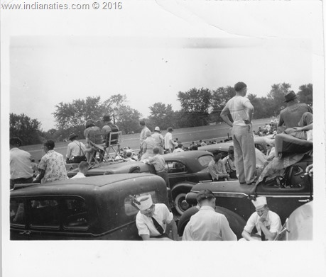 People situated on top of their cars in the infield of the Indianapolis Motor Speedway.