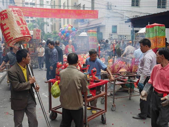 people preparing a location for prayer during the Nian Li Festival (年例节) in Maoming, China