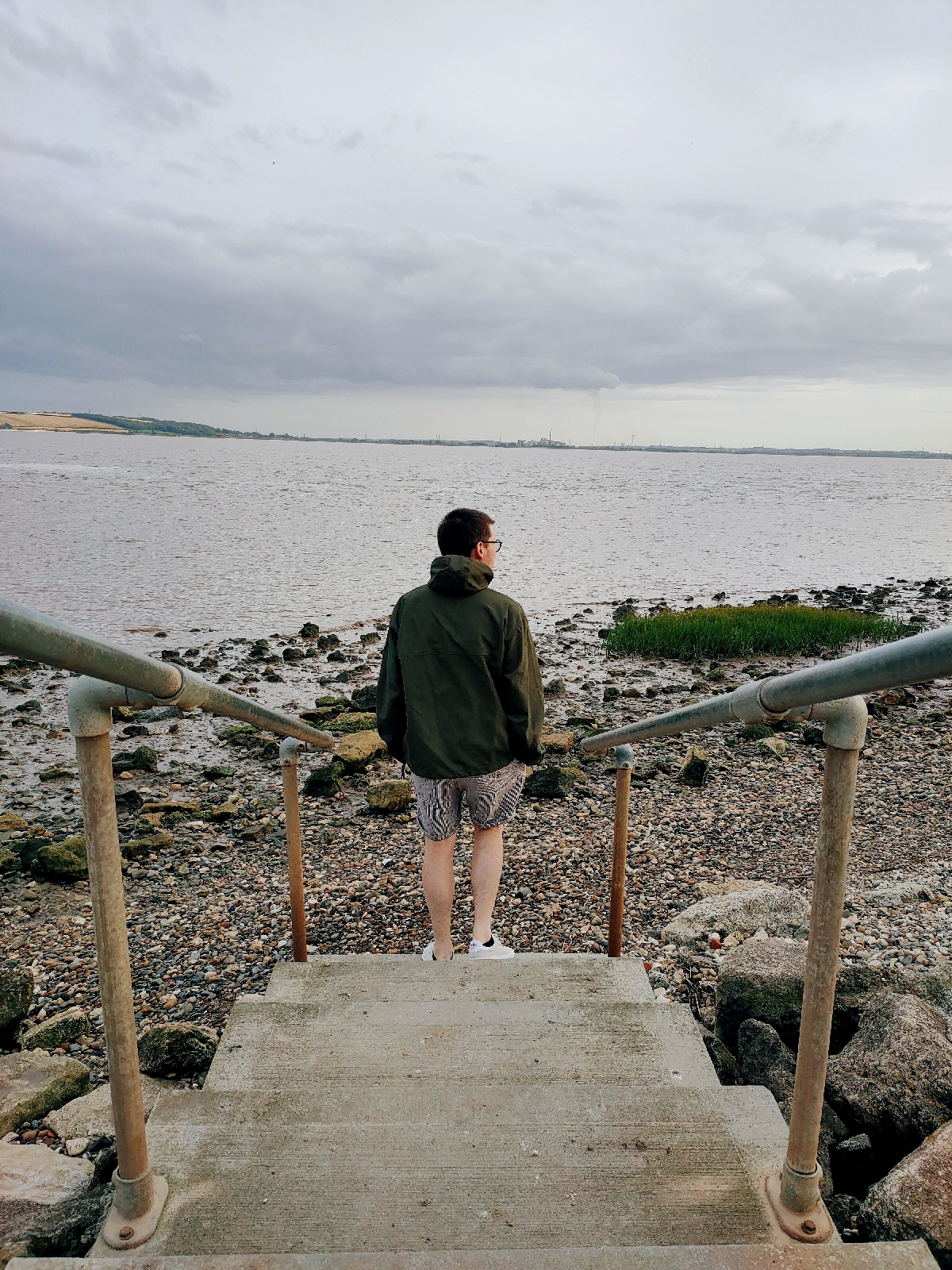 A man stood at the bottom of some steps leading to a pebbled foreshore next to a river.