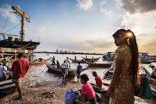 lokale bevolking bij een strandje met grote vracht-roeiboten