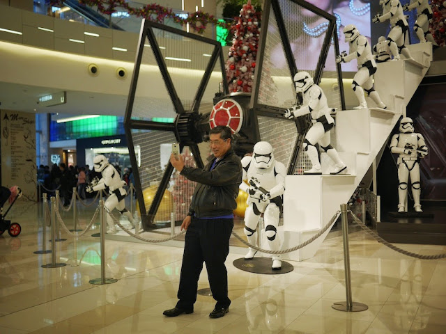 man taking a selfie in front of a Star Wars display at the IAPM shopping center in Shanghai