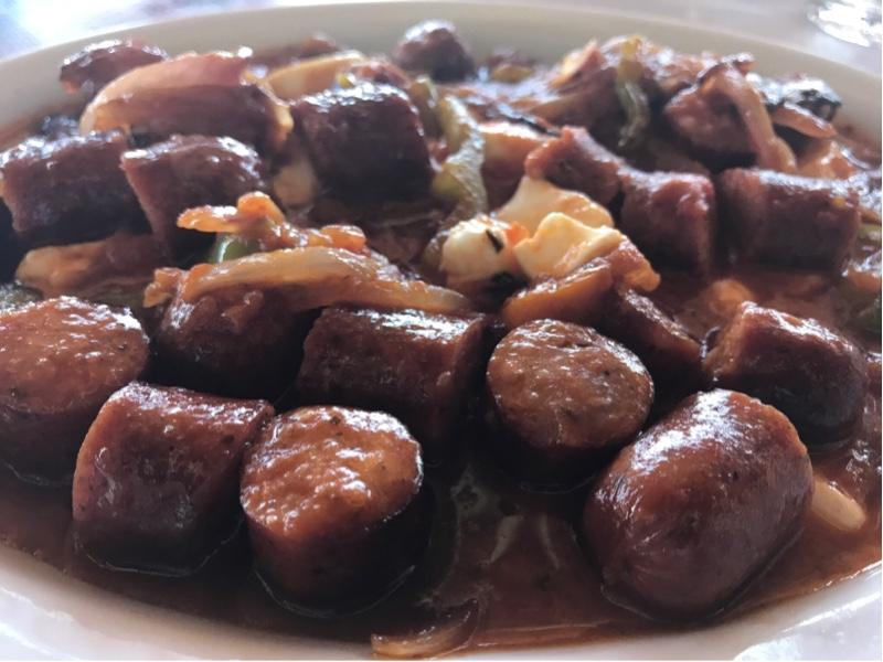 Pølsebiter i saus med biter av løk og smeltet fetaost.