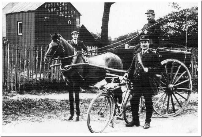 Shenley Postmen with bicycle and mail cart outside the postmen's shelter, c1909