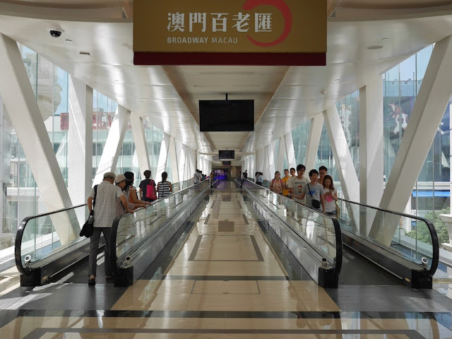 enclosed pedestrian bridge with moving walkways connecting Galaxy Macau with Broadway Macau