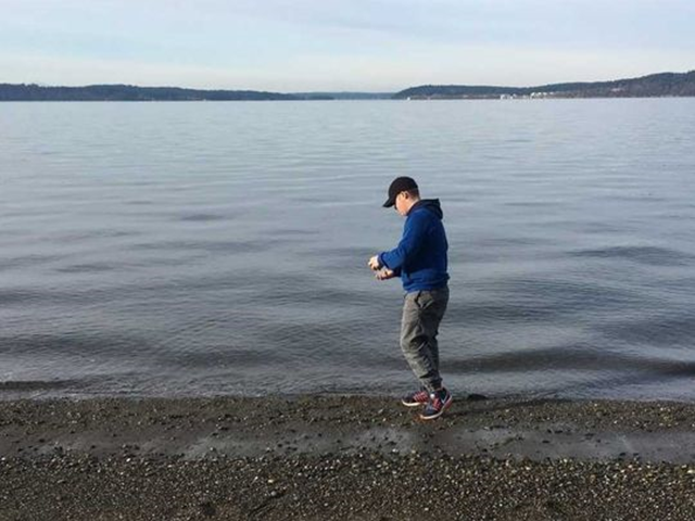 A volunteer gathers a water sample for the Puget Sound microplastic monitoring program. Photo: Kitsap Sun / contributed