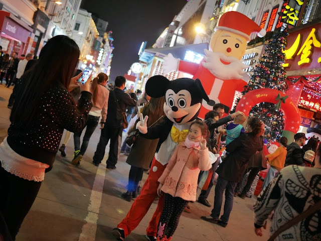 girl posing with a Mickey Mouse mascot at the Zhongshan Road Pedestrian Street in Xiamen