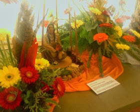 Injun sitting amongst a flower tribute display