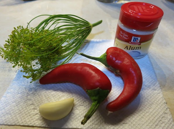 Use quart jars. In each jar put 1/8 teaspoon alum, garlic clove, red pepper...
