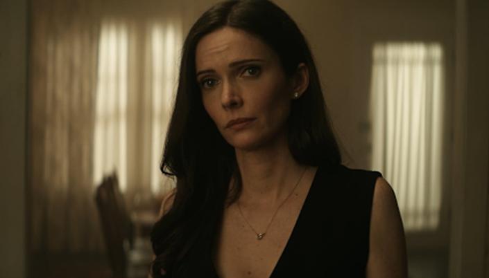 Lois Lane, usando vestido preto e colar, olha para a frente dentro da sala da casa.