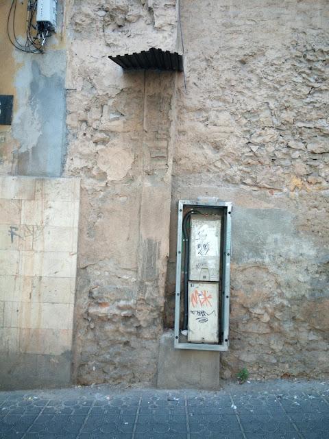 Un armari sense tapa a la vorera del carrer Gasòmetre amb uns tauladeta totalment desplaçada a l'esquerra. Vista frontal