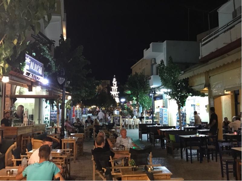 En gate om natten med mennesker som sitter og spiser.