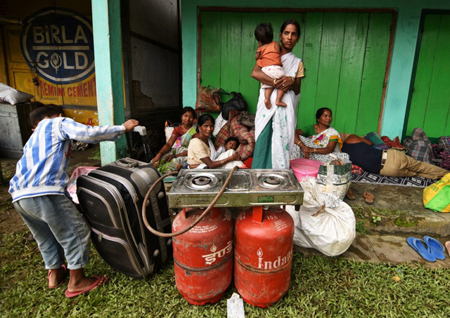 Flood-displaced families take shelter in front of a shop in the Jakhalabandha area of Nagaon district in Assam, India, 25 August 2017. Photo: Anuwar Hazarika / Reuters