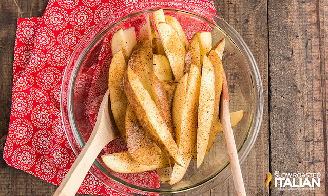 tossing fries with seasoning