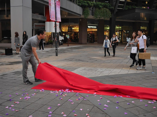 man folding up the red carpet